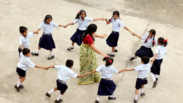 teacher playing with school students at school campus, haryana, india - school yard stock videos and b-roll footage