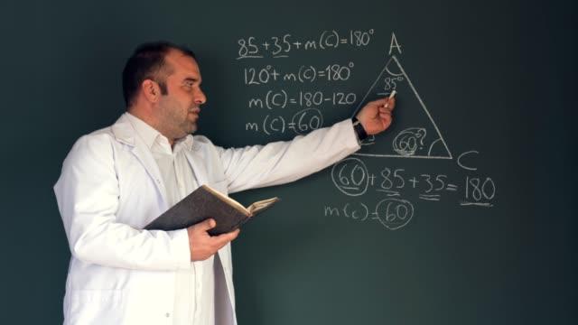 vidéos et rushes de professeur pointant avec le doigt à l'équation mathématique sur le tableau en classe - professeur d'université