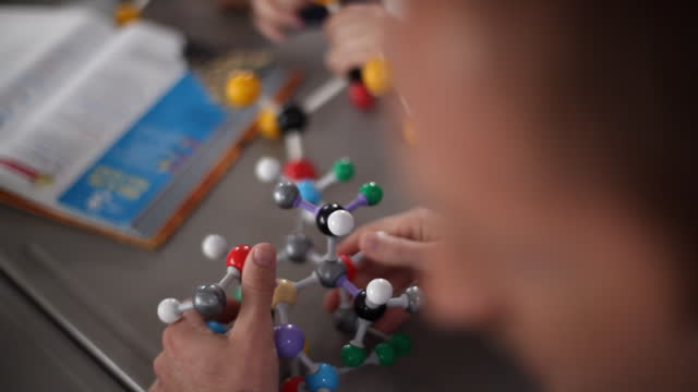 vídeos y material grabado en eventos de stock de a teacher prepares a molecular model for a lesson. - montar
