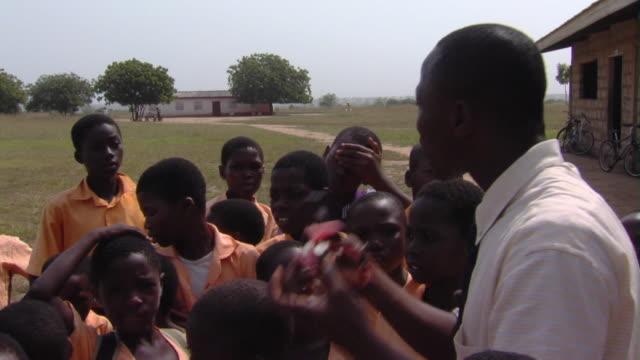 MS Teacher presenting solar power fan to children outdoors, Tamale, Ghana