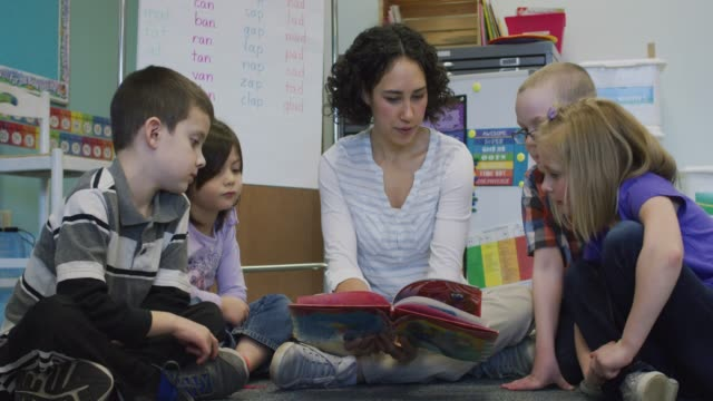 vídeos de stock, filmes e b-roll de professora de leitura no chão com os alunos em um meio-círculo - idioma