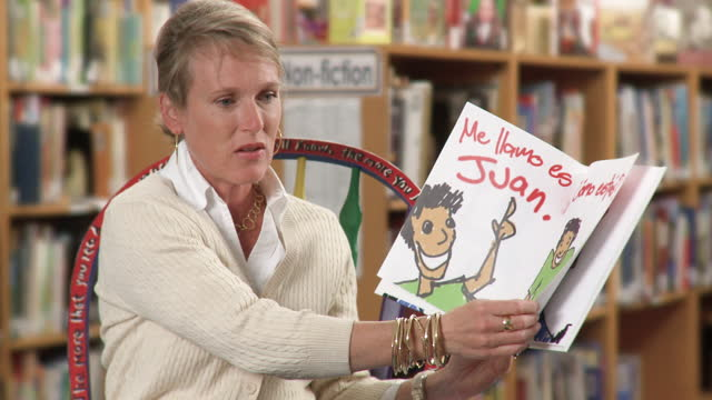 Teacher reading Spanish language book aloud to group of young students in school library