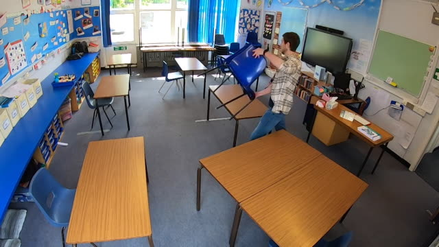 teacher setting primary school classroom up for social distancing moving desks during coronavirus pandemic - politics concept stock videos & royalty-free footage