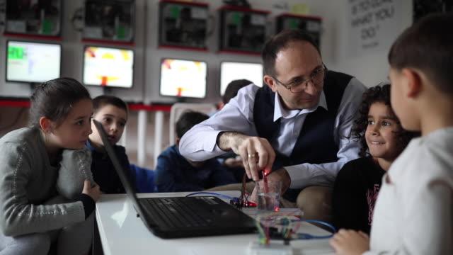vidéos et rushes de enseignant affichant des expériences d'ordinateur aux enfants - interactivité