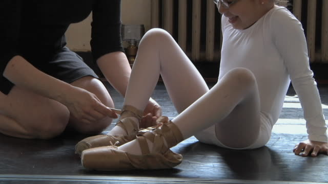 MS ZO Teacher showing student (4-5) how to lace toe shoes / Chicago, Illinois, USA