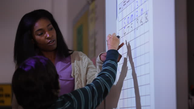 a teacher shows a student how to begin filling in a chart on the smartboard. - interactive whiteboard stock videos & royalty-free footage