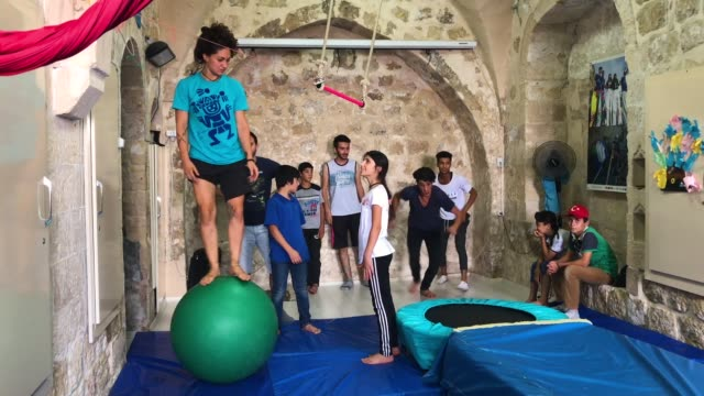 a teacher shows how to walk on a ball during an acrobatics workshop at the istasyon sirkhane center on july 24 2018 in mardin turkey the circus... - stilt house stock videos & royalty-free footage