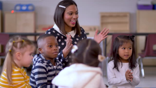 teacher sings and claps with children. - child care stock videos & royalty-free footage
