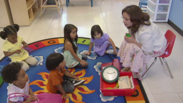 ha ms teacher sitting and talking to children in preschool classroom / san antonio, texas, usa - barnomsorg bildbanksvideor och videomaterial från bakom kulisserna