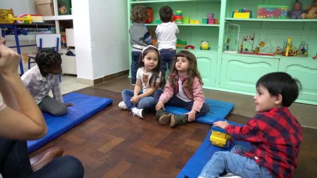 Teacher sitting with preschool students in school