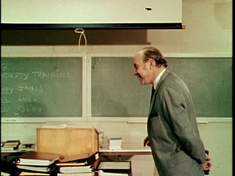 1970 MS MONTAGE Teacher speaking in front of chalkboard and pulling down screen, man starting movie projector, Los Angeles, California, USA, AUDIO