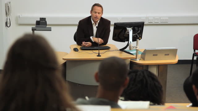 vidéos et rushes de ms ha selective focus teacher speaking in front of students in lecture hall / london, england - équipement audiovisuel