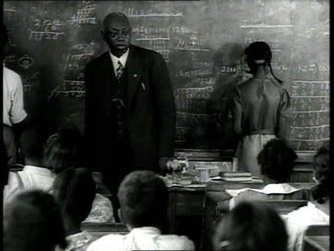 1939 ms teacher standing before class, students raising their hands, one student standing and walking to blackboard, where other students are working / usa - blackboard stock videos & royalty-free footage