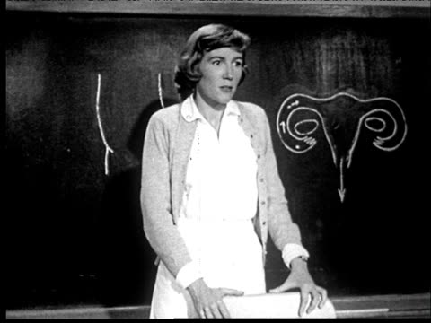 1953 B/W Teacher standing in front of blackboard drawing of uterus, talking to girls sitting at desks in classroom