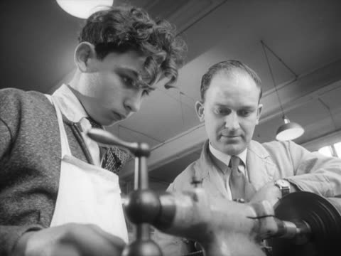 a teacher supervises a student while he uses a lathe during a metalwork lesson - metalwork stock videos & royalty-free footage