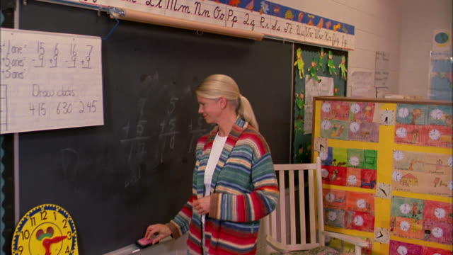 A teacher takes a bite from an apple after erasing the blackboard.