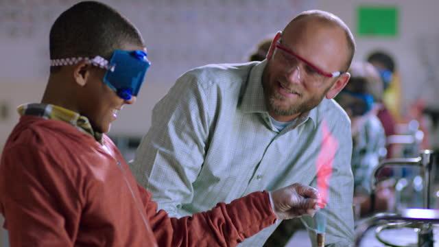 a teacher talk a smiling student through a bunsen burner experiment. - bunsen burner stock videos & royalty-free footage