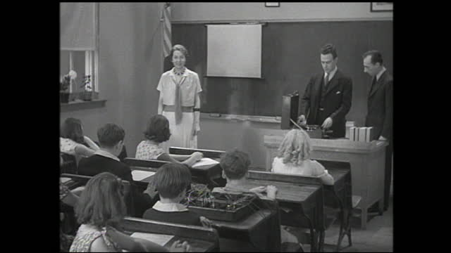 "teacher talking to girl inside classroom; title card: ""a few days later""; two men with suitcase standing in front of the classroom giving a... - 1940 1949 stock videos & royalty-free footage"