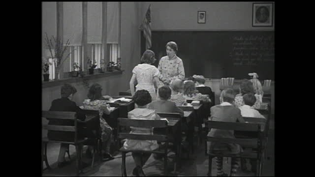 teacher talking to girl standing in the classroom while the children listens; vase falls off the window sill and everyone looks - 1940 1949 stock videos & royalty-free footage