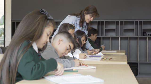 vidéos et rushes de professeur de parler à son élève corriger quelque chose sur son ordinateur portable - niveau primaire