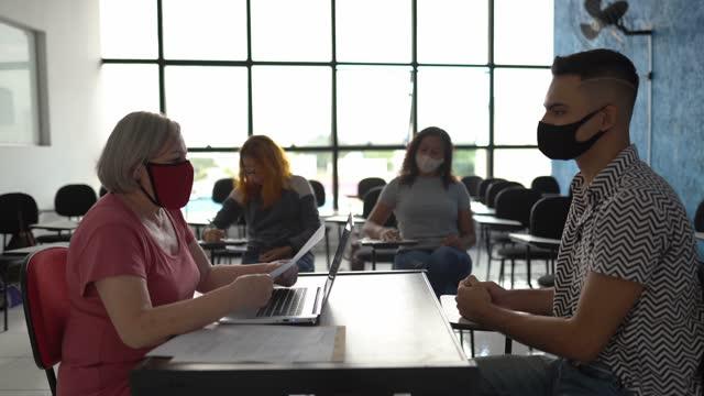 vidéos et rushes de enseignant parlant à l'étudiant au sujet des résultats d'essai à l'université ou faisant. un entretien d'embauche - porter un masque facial - demander