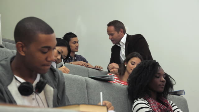 MS LA Teacher talking to students in lecture theatre / London, England