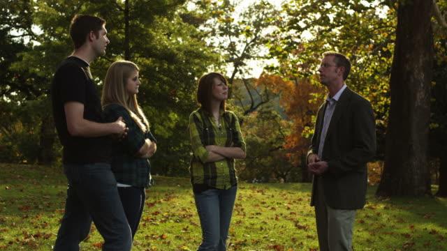 ms teacher talking to students in park, buena vista, virginia, usa - dreiviertelansicht stock-videos und b-roll-filmmaterial