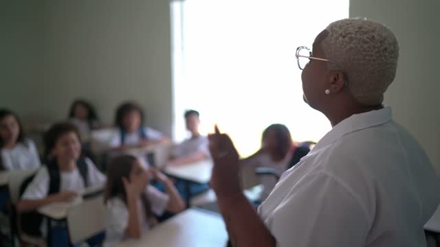 vídeos de stock e filmes b-roll de teacher talking to the class and being embraced by students at school - professora