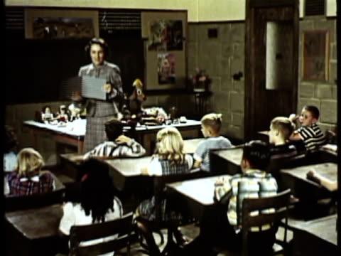 vidéos et rushes de 1953 montage ws teacher talking while showing class picture book, children raising hands sitting at desks / usa - salle de classe