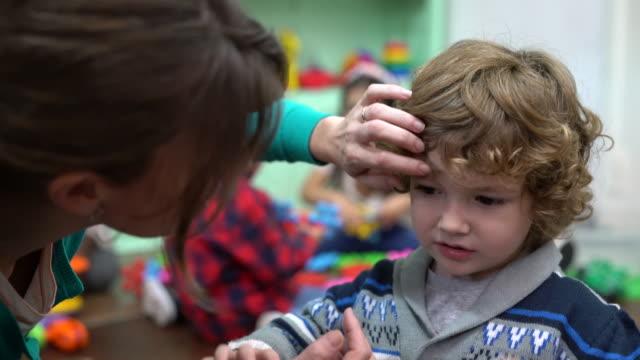 vídeos de stock, filmes e b-roll de professor falando ao mesmo tempo acariciando menino bonitinho na escola - acariciando