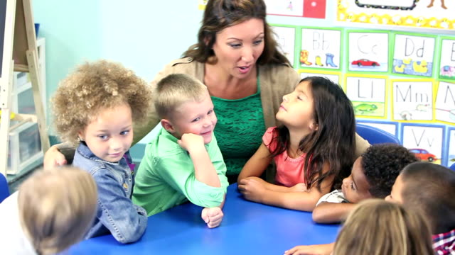 Teacher talking with her class of young school children