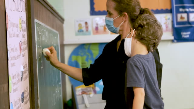 teacher teaching a pre school schoolboy both wearing protective face masks in the classroom - males stock videos & royalty-free footage