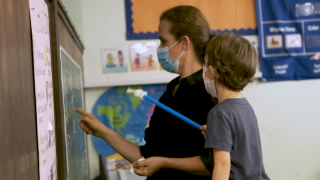 teacher teaching a pre school schoolboy both wearing protective face masks in the classroom - preschool stock videos & royalty-free footage
