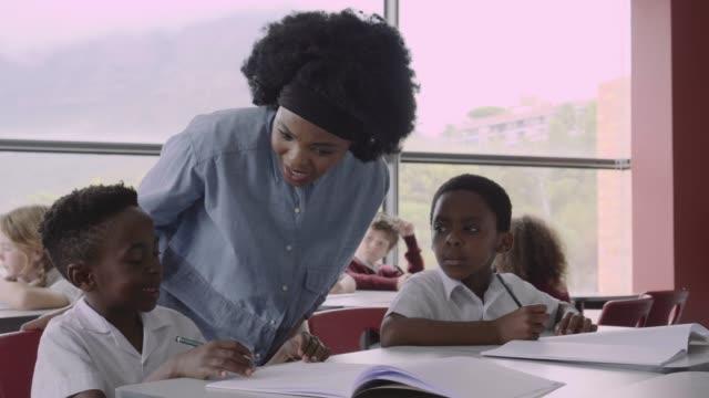 vídeos de stock, filmes e b-roll de teacher teaching boy at desk in school - caderno de anotação