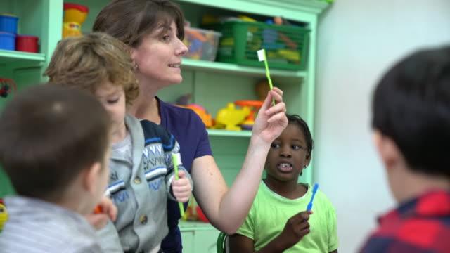 vídeos de stock, filmes e b-roll de professor ensinando escovar para alunos em sala de aula - cinco pessoas