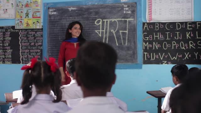 Teacher teaching her school students in a classroom