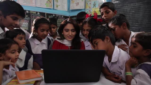 Teacher teaching her school students on a laptop