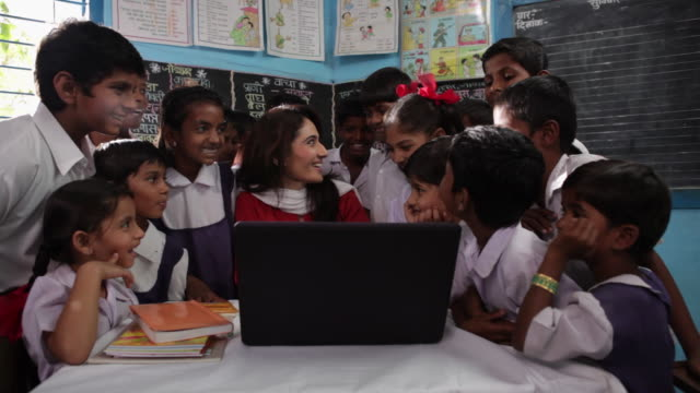 vidéos et rushes de teacher teaching her school students on a laptop  - montrer la voie