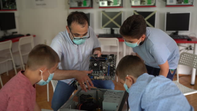 vídeos de stock e filmes b-roll de teacher teaching schoolboys about computer hardware on stem class in private school classroom - stem assunto