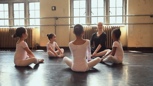 stockvideo's en b-roll-footage met ws teacher teaching stretching exercises to students (2-7) in ballet class / chicago, illinois, usa - gympak