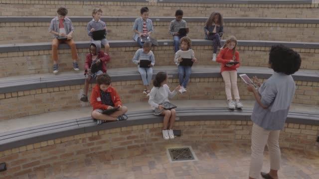vidéos et rushes de teacher teaching students through digital tablet - person in education