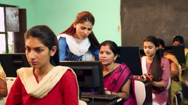 Teacher teaching to a adult woman in the classroom, Sonipat, Haryana, India