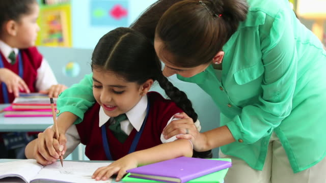 Teacher teaching to a schoolgirl in the classroom, Delhi, India