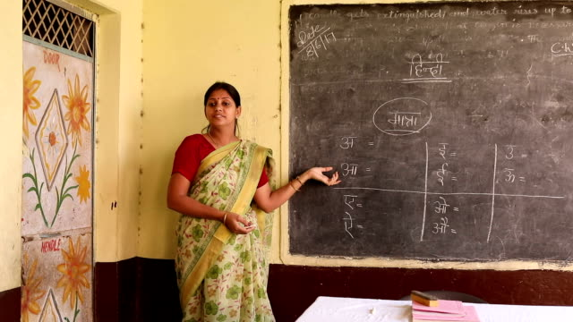 Teacher teaching to school students in classroom, Haryana, India