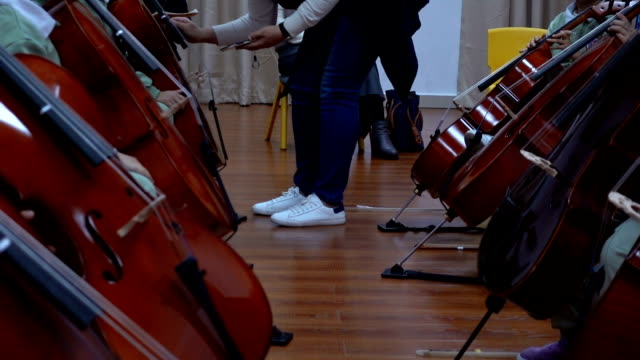 teacher tuning cello indoors - orchestra stock videos & royalty-free footage