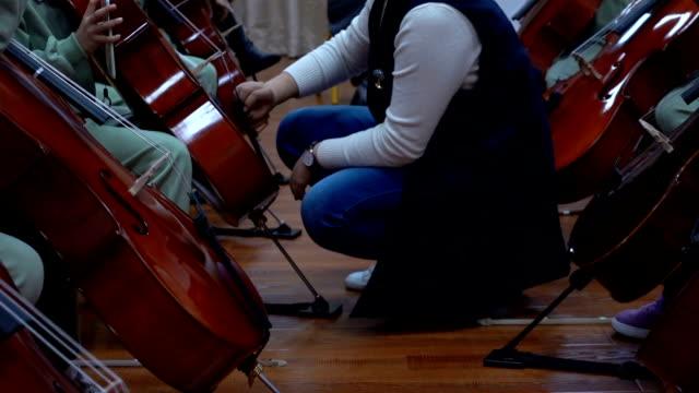 stockvideo's en b-roll-footage met leraar tuning cello binnenshuis - lus