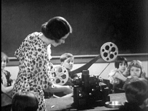 1935 B/W MS Teacher turning on movie projector in classroom with children about age 12 at desks / USA