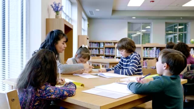 teacher tutors group of students after school - elementary age stock videos & royalty-free footage