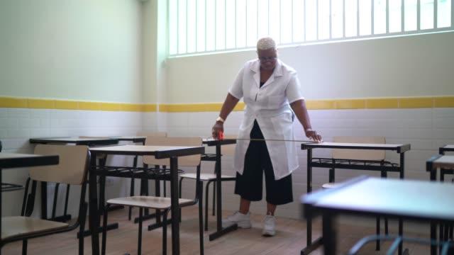 vidéos et rushes de l'enseignant utilise une mesure de bande pour mesurer la distance du bureau de l'élève afin de garder la distance sociale de l'élève dans la salle de classe - tape measure
