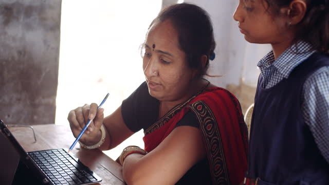 teacher using a smart digital device n her desk, laptop tablet, for teaching aid to a classroom of students - indian subcontinent ethnicity stock videos & royalty-free footage